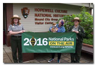 Rangers Susan Knisley and Nissa Salvan holding the NPOTA banner; Kate McFadden and puppy Bo in the center